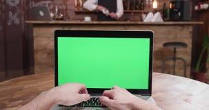 La paralaje POV tiró de la persona que mecanografiaba en el ordenador portátil con la pantalla verde encendido almacen de video