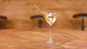 La paralaje tiró de un vidrio de martini en una tabla de madera vacía almacen de metraje de vídeo