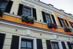 La pared de la casa con las ventanas con los obturadores y las macetas Foto de archivo