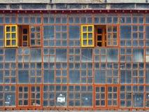 La pared de cristal, consistiendo en marcos de madera del color marrón con el vidrio en el cual se refleja el cielo azul, dos ven Foto de archivo libre de regalías