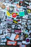 La pared de la calle cubrió etiquetas engomadas multicoloras numerosas Imágenes de archivo libres de regalías