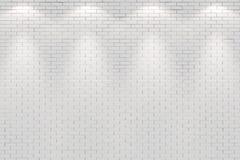 La pared de ladrillo blanca en blanco se encendió por cuatro luces del punto