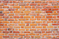 La pared de ladrillo con rojo, la naranja y el amarillo coloreó ladrillos Foto de archivo