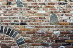 La pared de ladrillo roja vieja con granito empiedra la inserción, el arco y la floración Imágenes de archivo libres de regalías