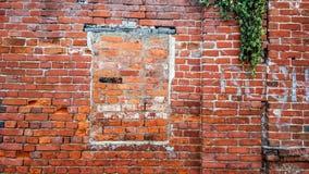 La pared de ladrillo, la ventana bricked, el ladrillo rojo del cemento viejo en el verano en la ciudad, un edificio se abandone q Fotos de archivo libres de regalías