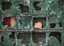 La pared de los bloques de cristal está quebrada por las piedras imágenes de archivo libres de regalías