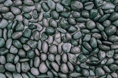 La pared de piedra de los guijarros negros adorna el fondo de la textura Imagenes de archivo