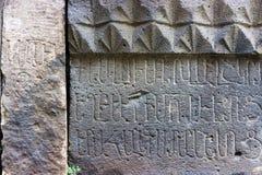La pared de piedra talló con las letras en el alfabeto armenio, lengua Foto de archivo