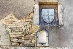 La pared de piedra vieja con los lugares y el escudo de madera sellan en Borgoña, Francia Foto de archivo libre de regalías