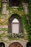 La pared de piedra vieja con una boda adornó la ventana Fotografía de archivo libre de regalías