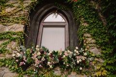 La pared de piedra vieja con una boda adornó la ventana Imagenes de archivo