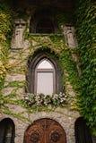 La pared de piedra vieja con una boda adornó la ventana Foto de archivo