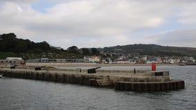 La pared del puerto con el canon en la costa sur inglesa BRITÁNICA de Lyme Regis Dorset England almacen de video