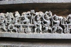 La pared del templo de Hoysaleswara talló con la escultura de guerreros y de la escena de batalla antigua Fotografía de archivo libre de regalías