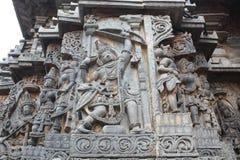 La pared externa del templo de Hoysaleswara talló con la escultura de Arjuna al gran arquero con su arco Imagenes de archivo