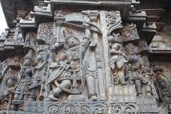 La pared externa del templo de Hoysaleswara talló con la escultura de Arjuna, el gran arquero con su arco Foto de archivo libre de regalías
