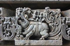 La pared externa del templo de Hoysaleswara talló con la escultura de dios de Varuna de la lluvia que marchaba en su animal mític Imágenes de archivo libres de regalías