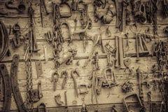 La pared llenó de las herramientas viejas que colgaban en la pared Imágenes de archivo libres de regalías