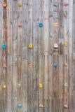 La pared que sube de madera vieja con el dedo del pie y la mano sostienen los pernos prisioneros Foto de archivo libre de regalías