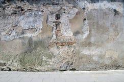 La pared quebrada cerca a la acera. fotografía de archivo