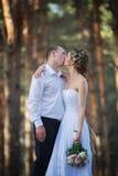 La pareja casada alegre de los jóvenes se está besando Fotografía de archivo libre de regalías