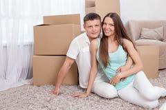 La pareja casada los jóvenes alegres se está moviendo en otra Foto de archivo libre de regalías