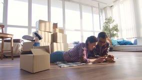 La pareja casada los jóvenes miente en el piso contra la perspectiva de las cajas para moverse almacen de metraje de vídeo