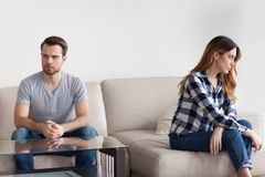 La pareja de matrimonios obstinada infeliz siente la sentada frustrada enojada en el sofá imagen de archivo libre de regalías