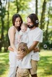 La pareja de matrimonios vestida en la ropa blanca es sonriente y que detiene a poca hija en los brazos mientras que abraza al hi imagen de archivo libre de regalías