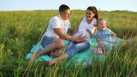 La pareja embarazada con la hija del niño tiene campo de hierba del outdoorsin del tiempo libre en la manta metrajes