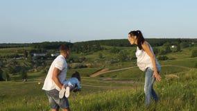 La pareja embarazada con la hija del niño tiene tiempo libre al aire libre almacen de video