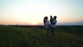 La pareja embarazada con la hija del niño tiene tiempo libre al aire libre en la puesta del sol almacen de metraje de vídeo