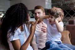 La pareja hermosa se está sentando en el sofá con su pequeño hijo mientras que teniendo una pelea fotografía de archivo libre de regalías