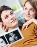 La pareja hermosa se imagina el futuro de su niño nonato Imagen de archivo libre de regalías