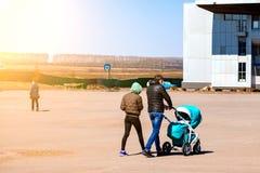 La pareja joven de la familia con la mam? y el pap? est?n caminando al aire libre con un cochecito de beb? del color azul en el c imágenes de archivo libres de regalías