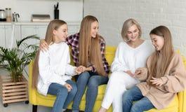 La pareja lesbiana joven feliz con dos hijas hermosas con el pelo largo, visti? todo casual imagen de archivo