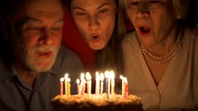 La pareja mayor cariñosa y su hija celebran con la torta en casa Abrazando y soplando hacia fuera velas almacen de metraje de vídeo