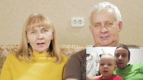 La pareja mayor comunica con el hijo y el nieto en Internet PIPA: vea a la familia entera en la pantalla Papá y almacen de metraje de vídeo