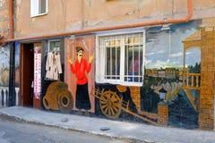 La parete artisticamente dipinta variopinta di vecchia casa nella vecchia parte di Tbilisi ha descritto la scena di vita quotidia immagini stock libere da diritti