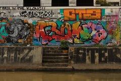 La parete completamente coperta dai graffities luminosi della via a Bangkok, Tailandia Immagine Stock