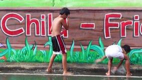 La parete concreta della scuola dipinta murale è un posto in cui due bambini godono del bagno della pioggia archivi video