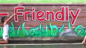La parete concreta della scuola dipinta murale è un posto in cui due bambini godono del bagno della pioggia stock footage