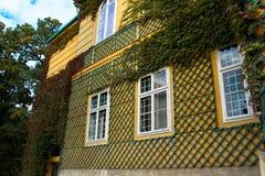 La parete della casa è coperta di grata di legno fotografie stock libere da diritti