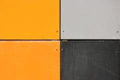 La parete della casa, sistemata con i pannelli variopinti, dipinti nei colori luminosi Grey ed arancia Fotografie Stock