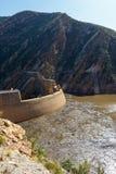 La parete della diga costruita accanto alle montagne fotografie stock