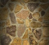 La parete di massoneria con le pietre irregolari si è illuminata da sopra Fotografia Stock Libera da Diritti