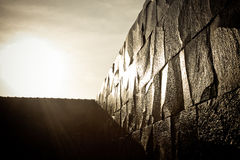 La parete di pietra scura e bagnata splende con luce solare diretta Immagine Stock