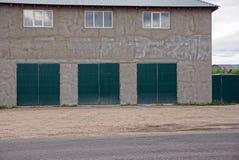 La parete grigia di grande casa con le finestre e tre rivestono di ferro i portoni del garage sulla via fotografia stock