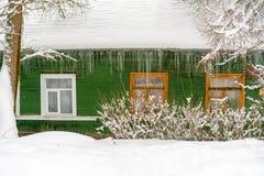 La parete verde della casa di legno di vecchio-modo russo con le finestre di legno, il tetto coperto da neve ed i ghiaccioli enor fotografia stock libera da diritti