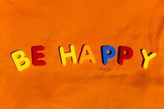 La parola è felice composta dalle lettere variopinte del giocattolo dei bambini Fotografie Stock Libere da Diritti
